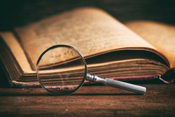 Vintage book and magnifying glass on wooden background