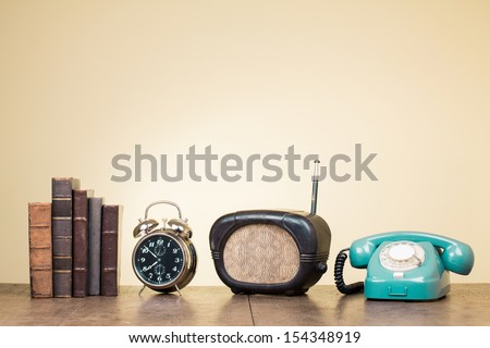 Vintage books, alarm clock, old radio, retro telephone on wood table