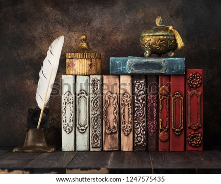 Vintage books on a shelf, ancient caskets, manuscript and antiquarian inkwell with a feather. Retro still life