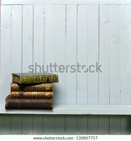 Vintage books on shelf; photographed in a pile against a pale, rustic wall; good copy-space