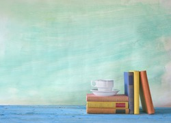 vintage books with coffee cup, grungy background, free copy space