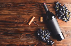 Vintage bottle of red wine with blank matte black label, corkscrew & bunches grapes on wooden table background. Expensive bottle of cabernet sauvignon concept. Copy space, top view, flat lay.