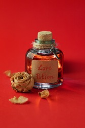 Vintage bottle with magic love potion and dried rose on red background