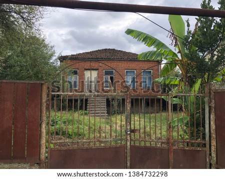 Vintage brick house with metal fence. Metal corrosion. Iron fence with rust. Walk through the streets of Batumi.