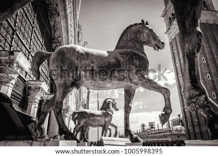Vintage bronze horses of St Mark`s Basilica over the St Mark`s Square (San Marco) in Venice, Italy. Famous ancient architecture and art in Venice. Black and white photo of Venice landmark.