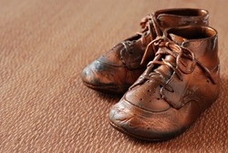 Vintage bronzed baby shoes on textured lacewood.  Macro with shallow dof.  Copy space included.