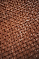 Vintage brown braided leather texture. Leather woven together. Abstract clothing background. Natural material. Shallow depth of field. Closeup.