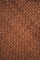Vintage brown braided leather texture. Leather woven together. Abstract clothing background. Natural material. Vertical photo.