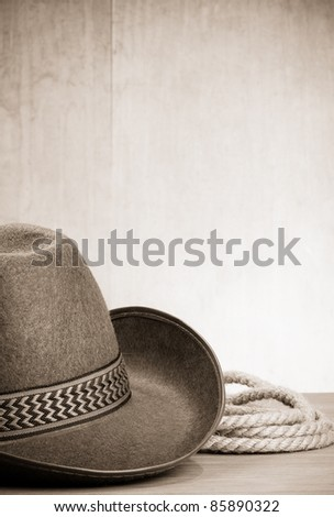 vintage brown cowboy hat and rope at wood background on sepia