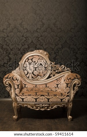 vintage brown-gray chair with gold accents standing beside the wall. wooden floor