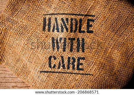 Vintage Burlap Bag with Handle with Care word text screen for Concept and Idea of Food, Art, Object, Kitchen Background and Textured, Country Rustic Still Life Style.