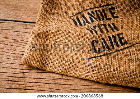 Vintage Burlap Bag with Handle with Care word text screen on Wood Table for Concept and Idea of Food, Art, Object, Kitchen Background and Textured, Country Rustic Still Life Style.