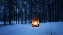 Vintage burning lantern on snow. Dark forest on background. Night forest. Winter season. Copy space.