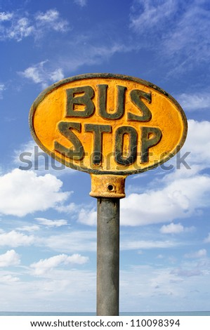 vintage bus stop sign with a blue sky background.