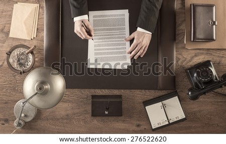 Vintage businessman in the office reading and signing a contract sitting at his desk, top view