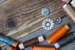 vintage buttons and threed on the textured surface of the ancient tailor's table