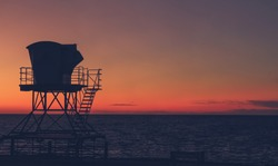 Vintage California sunset with life guard station silhouette