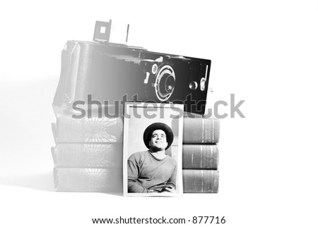 Vintage camera, books and photograph of a young man (circa 1946) in black and white.