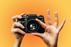 Vintage Camera in female hand. A photo. Photographer. Manual focus. Colored background. orange