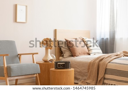 Vintage camera on round wooden table in the middle of elegant bedroom with retro armchair and single bed with beige bedding and flowers in vase