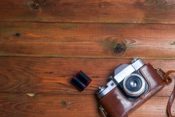 Vintage camera on wooden boards abstract background. Copy space for text. Top view.