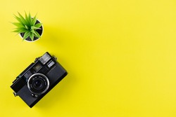 Vintage camera on yellow background with copy space. World photography day conept.