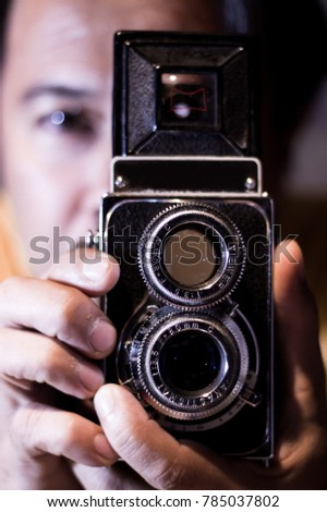 Vintage Camera Photographer Focus Shooting concept. Man with old vintage camera in hands. Focus to man eyes. Vintage stylized photo of man photographer with old TLR Camera, ring-flash shot.