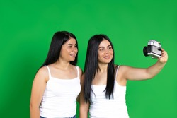 Vintage camera. Twin girls smile and take pictures. Photo on a green background.