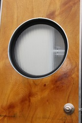 Vintage camper circle window with metal and wood detail and striped glass.