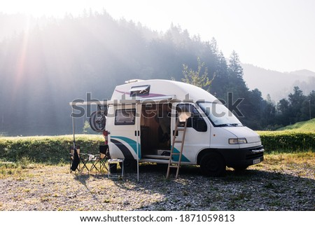 Vintage camper van parked on campground or camping in forest. Beautiful sunny morning in wild camp spot. Nomadic vanlife lifestyle. Relaxed simple vacation. RV camping destination