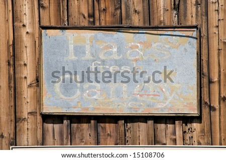 Vintage candy sign on log cabin wall