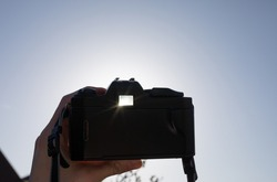 vintage canon film camera being held up high in the sky strongly backlit