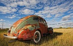 Vintage car rusting in a prairie field