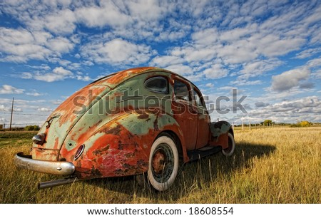Vintage car rusting in a prairie field