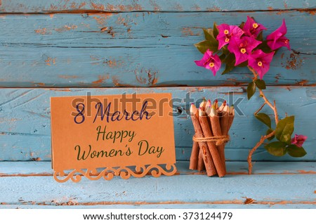 vintage card with phrase: 8 march happy womens day on wooden texture table next to purple bougainvillea flower.