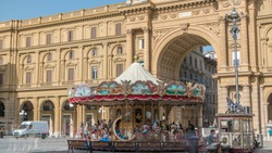 Vintage carousel and tourists in Piazza della Repubblica (Republic Square) and the arch in honor of the first king of united Italy on background in Florence, Italy.