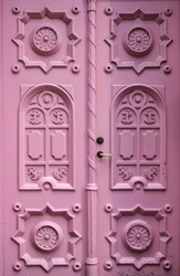 Vintage carved wooden door painted in vivid pink color, Tallinn. close up view