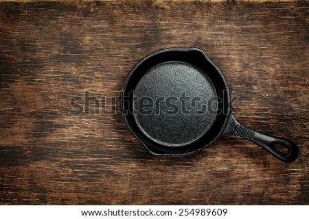 Vintage cast iron skillet on rustic wood background. Food background with copyspace
