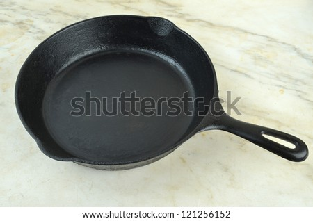 Vintage Cast Iron Skillet sitting on old marble kitchen counter top. - stock photo