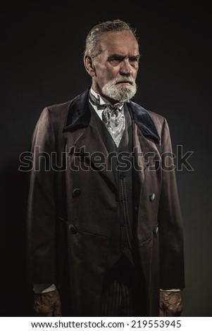 Vintage characteristic senior man with gray hair and beard. Studio shot against dark background.