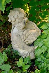 Vintage cherub statue nestled in nature's leaves.