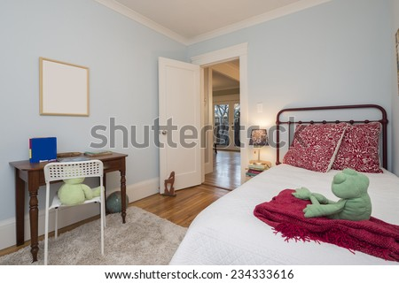 Vintage children bedroom / kids room with light blue walls, carpet, chalk board, books and wooden desk with white chair.