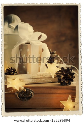 Vintage Christmas Card with Gifts, box, white ribbon and pine cones, retro photo frame