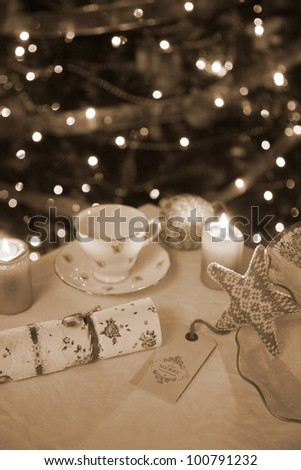 Vintage Christmas Decorations on a table top with antique,baubles,cracker,tea cup and cake stand, - stock photo