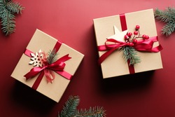 Vintage Christmas gift boxes wrapped kraft paper, wooden decorations, fir branches on marsala red background. Merry Christmas celebration concept.