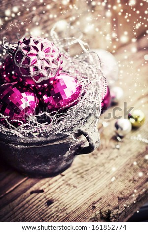 Vintage Christmas Ornament Background/ Christmas decorations in old pot on textured wooden background/ Composition with Brilliant Christmas Balls