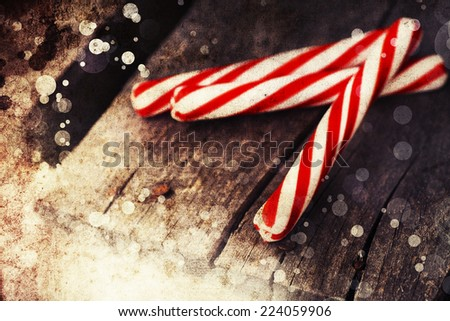 Vintage Christmas Ornament Background/ Christmas decorations red and white candy canes on textured wooden background/ Composition with Brilliant Christmas decoration