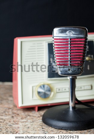 Vintage chrome and red microphone with a vintage 50's style radio in the background - stock photo