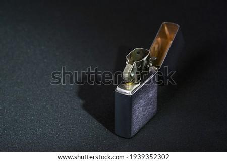 Vintage chrome steel gasoline lighter. Windproof lighter on a black background, close-up. ストックフォト ©