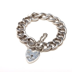 Vintage Chunky silver charm bracelet with heart shape lock isolated against white.
